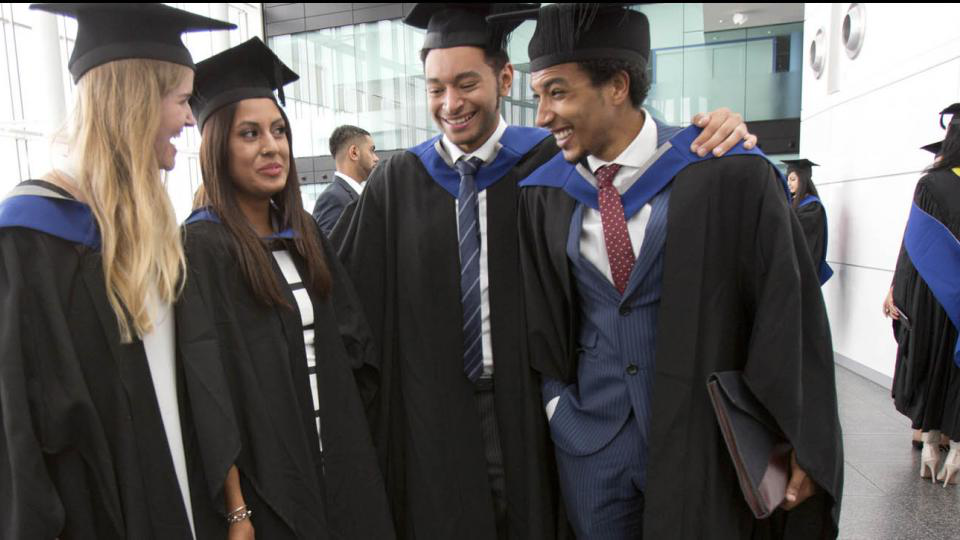 Four graduands laughing and smiling