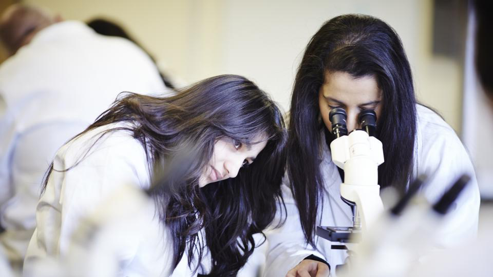 Two forensic science students with a microscope