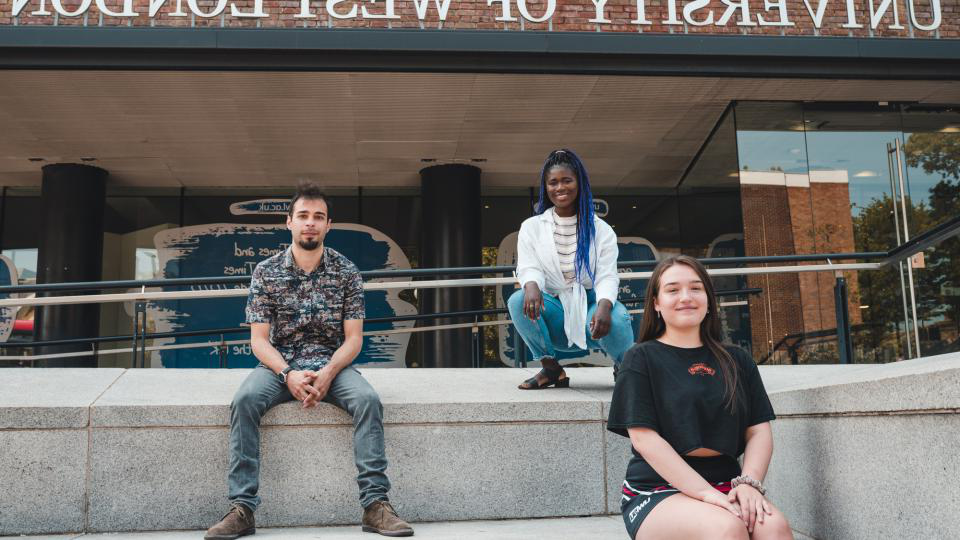 Students sitting on the steps outside a UWL building.