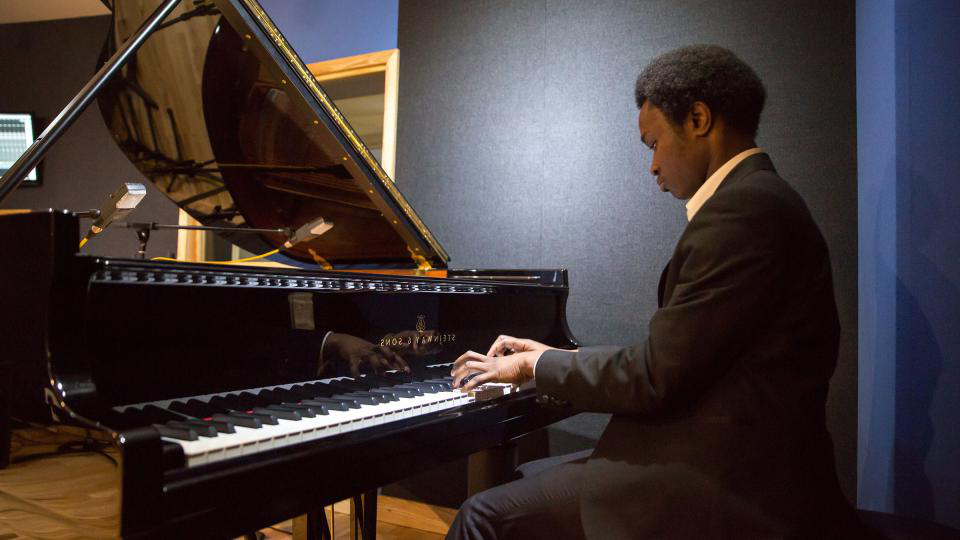 A man in a suit playing the piano in a studio